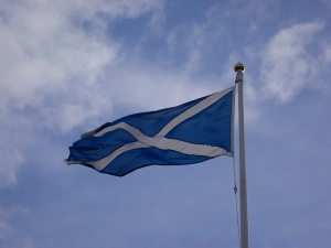 A saltire flag against a blue and cloudy sky